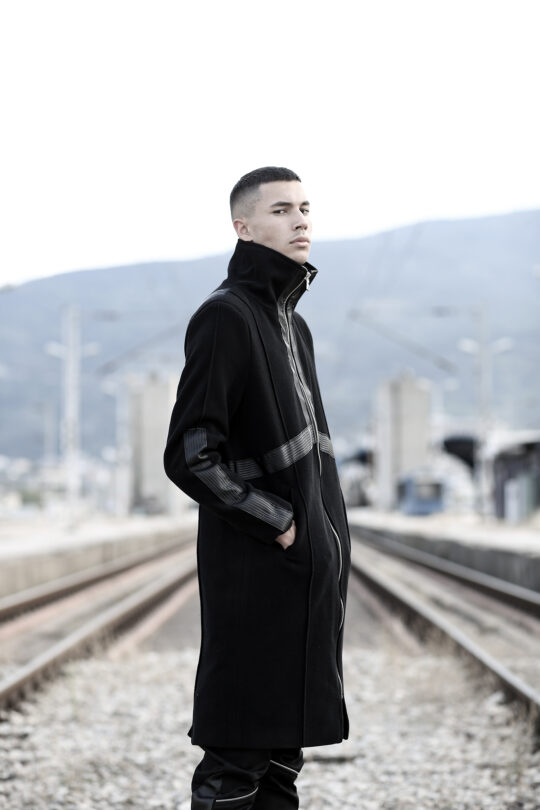 Man's Black long coat made of quality blend wool felt designed with faux leather, with lining. With pockets. Slim fit. Alternative clothing.