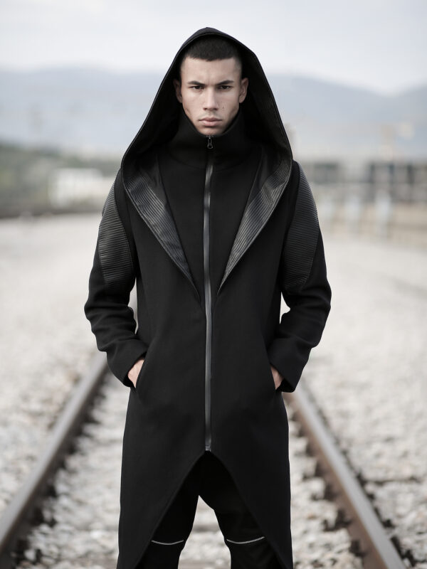 Black coat made of quality blend wool felt designed with faux leather, with lining. With pockets. Slim fit. Alternative style, futuristic look